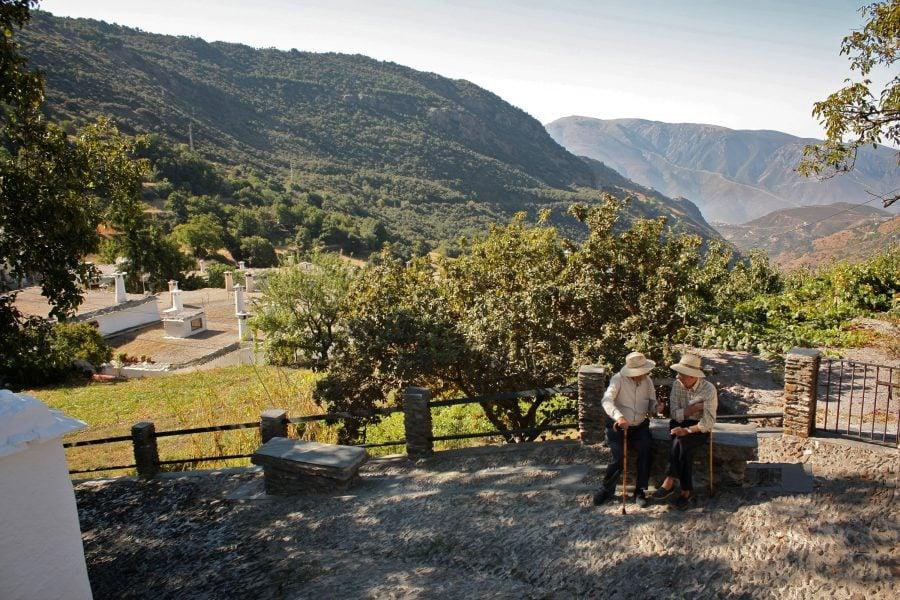 Doi bătranei stau de vorbă pe o bancă în Bubion, Valea Poqueira, Alpujarras