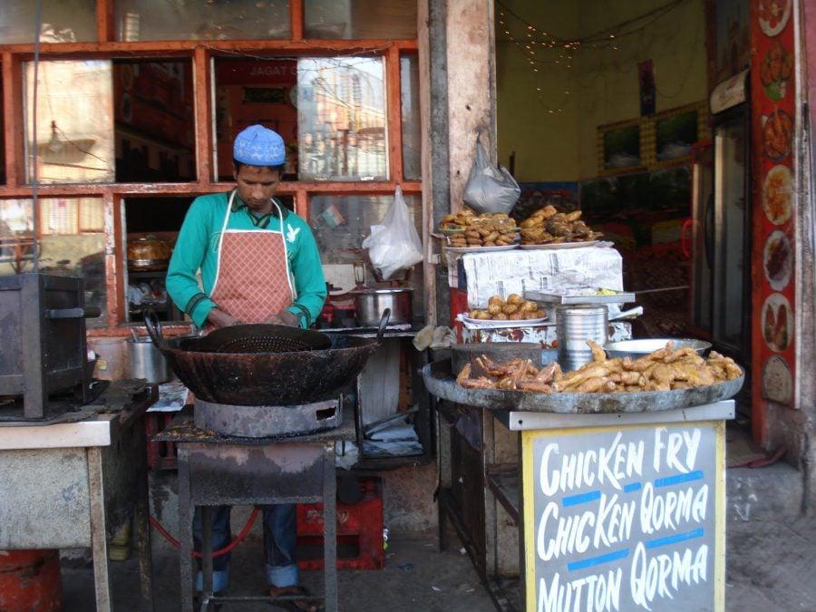Vânzător indian la o tarabă cu pui prăjit pe stradă în New Delhi, India