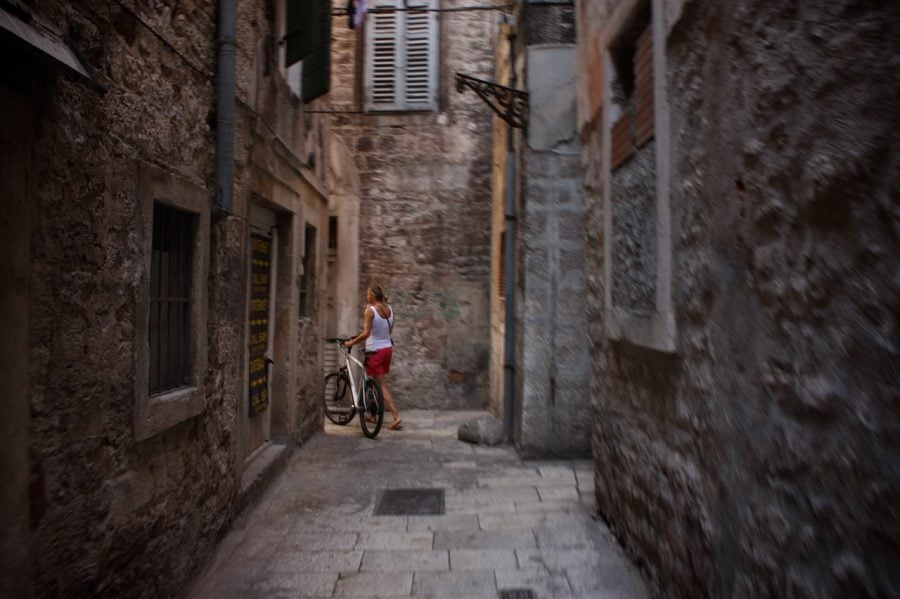 Fată cu bicicletă pe străduță ingustă din Split, Croația
