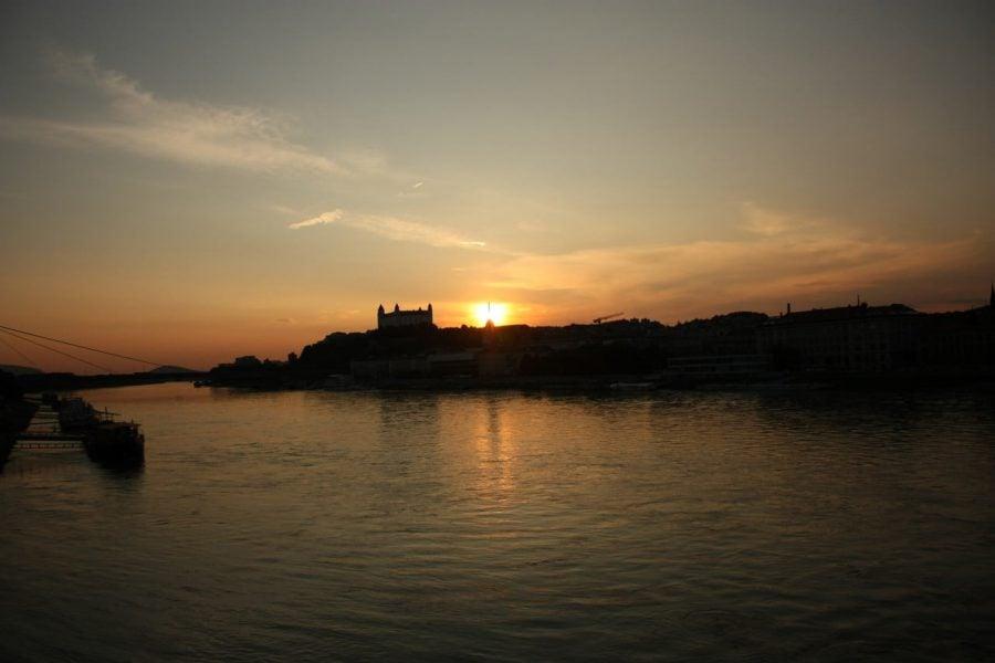 Soarele apune în spatele castelului Bratislava, priveliște de pe podul vechi (Stary Most)