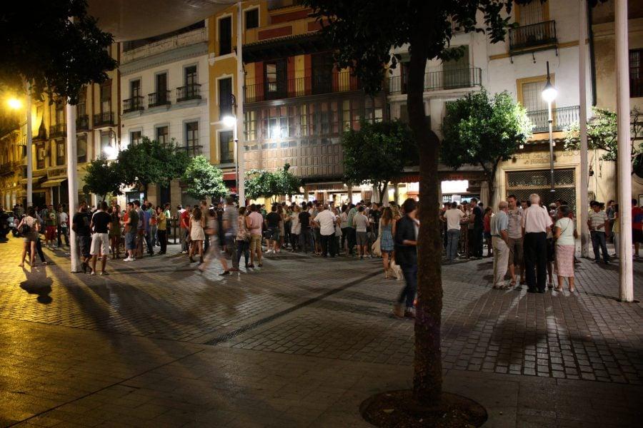 Spanioli pe stradă noaptea în Sevilia
