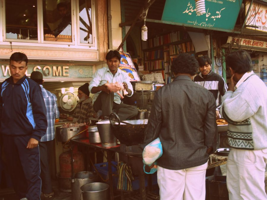 Oameni și tarabe pe o stradă din New Delhi, India