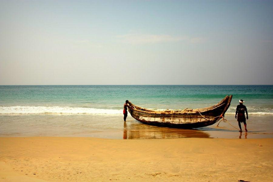 Pescari și barca lor pe plaja din Kovalam, Kerala, India