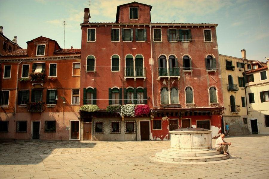Clădire cu multe ferestre și piață cu fântnă în Veneția