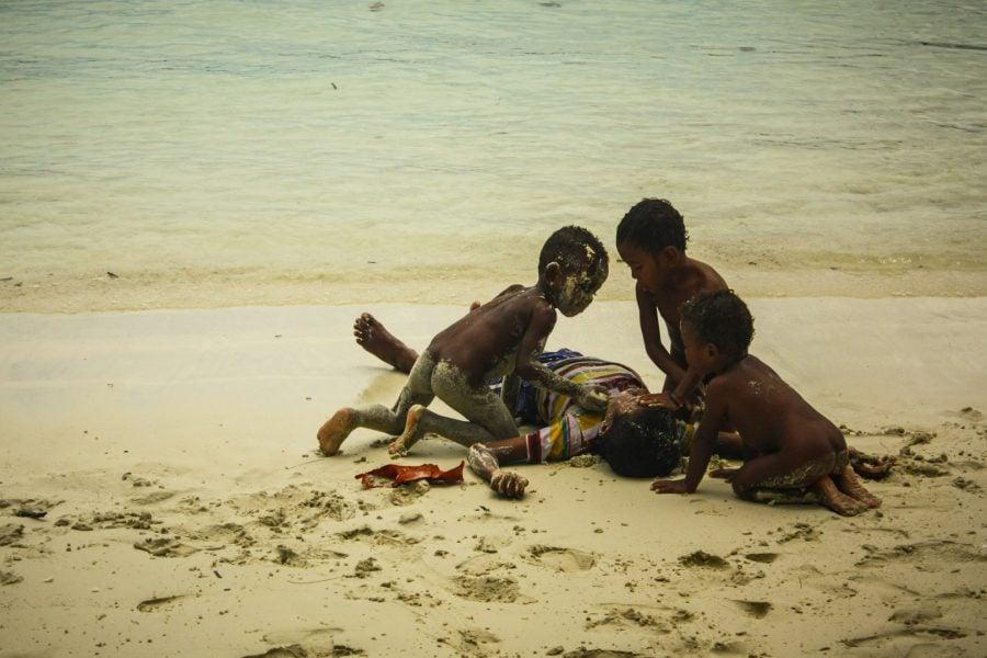 Copii papuani pe nisip alb